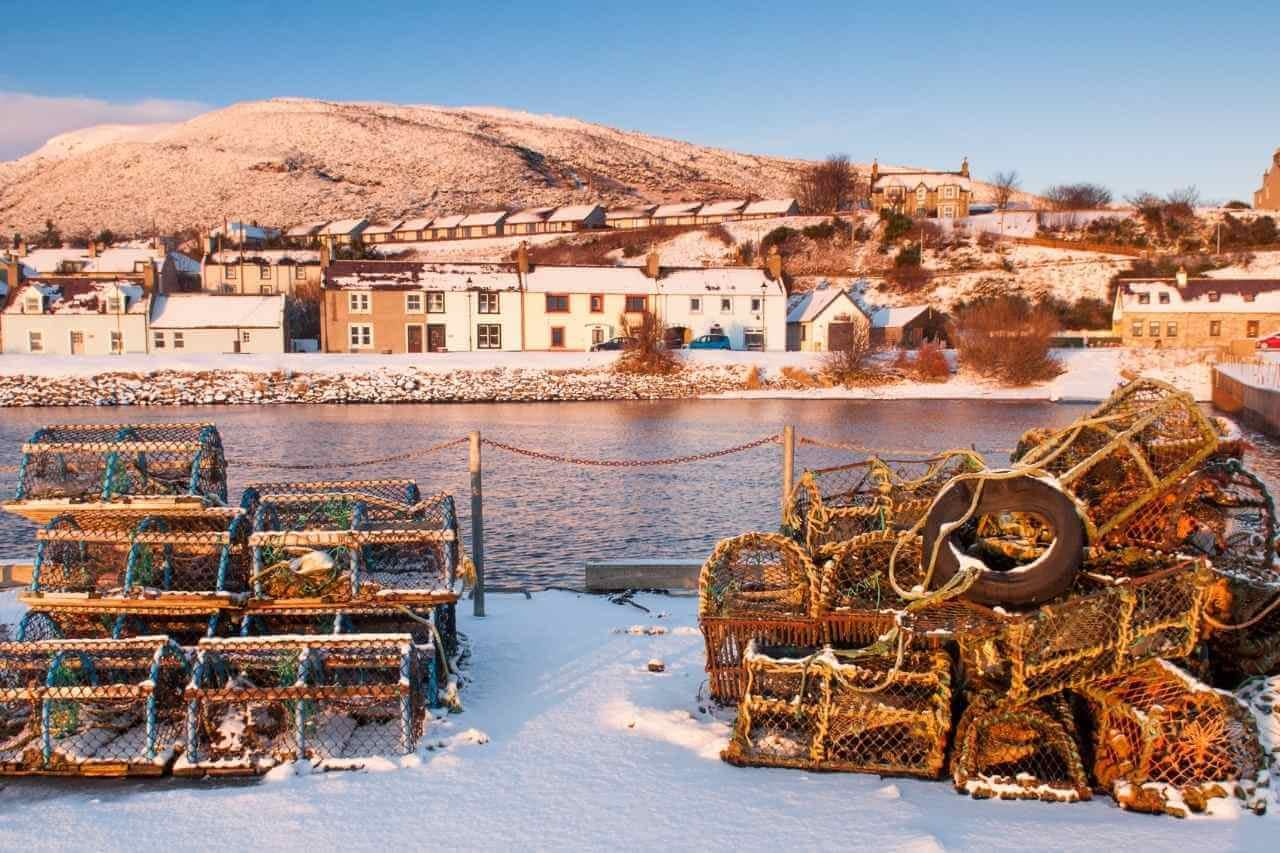 Helmsdale Harbour in the Snow. Lobster Pots stacked.